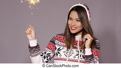 Young woman celebrating Christmas with a sparkler - Fun...