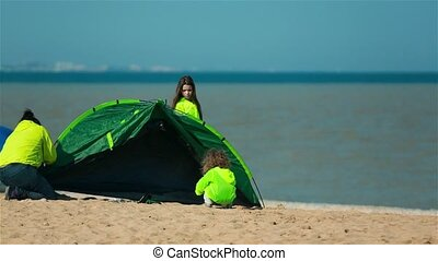 Woman with child establishes tent on the shore of the bay for a family holiday.