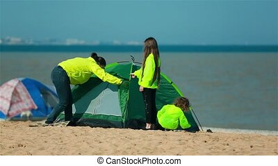 Mother with kids preparing a tent on the beach for families....