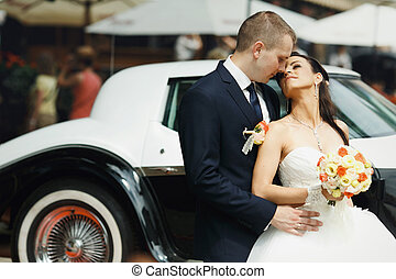 Bride and groom hugs in the front of old car