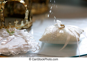 Wedding rings on the white pillow being blessed with a holy water