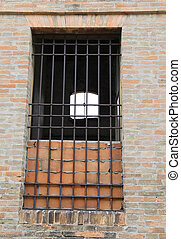 broken window of an abandoned house with iron bars and...