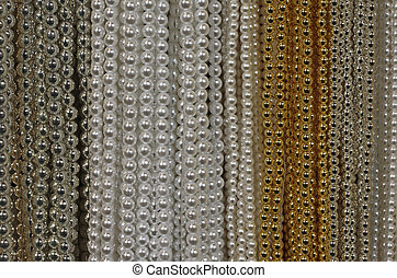 background of precious necklaces of gold beads silver and...