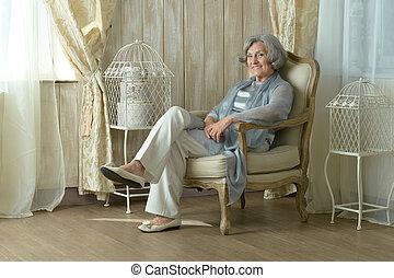elderly woman on chair in vintage room