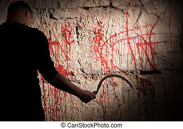 Man holding a sickle near blood stained wall for concept...