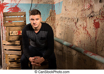 Young male sitting on empty packing crates in terrible...