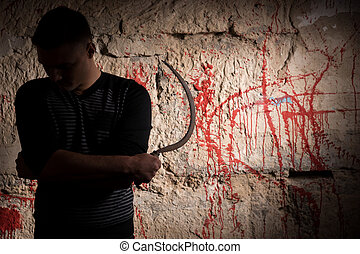 Man holding a sickle standing near blood stained wall for...