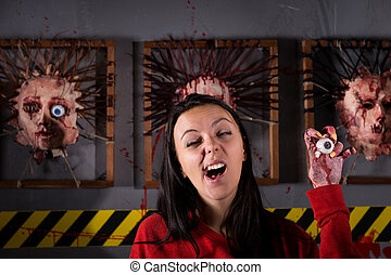 Single young strange woman yawns while holding eyeball in...