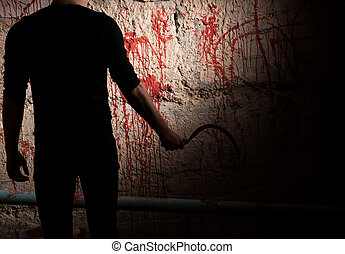 Shadowy male figure near blood stained wall - Shadowy male...