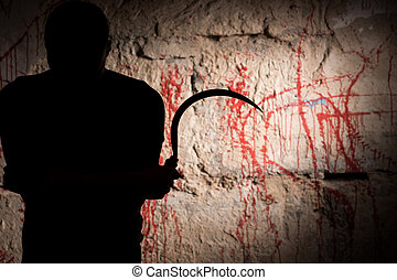 Portrait of shadowy figure holding blade near blood stained...