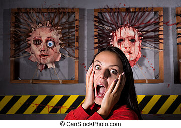 Scared woman in front of skinned faces for scary Halloween...
