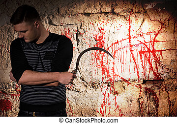 Portrait of a man holding a blade standing near blood...
