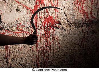 Male hand holding a sickle in front of blood stained wall in...