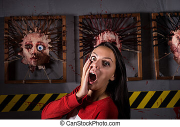 Scared attractive woman in front of skinned faces for scary...