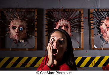 Scared young woman in front of skinned faces for scary...