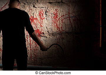 Shadowy male figure holding sickle near blood stained wall...