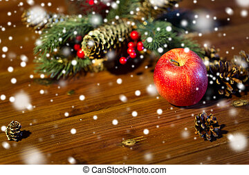 close up of apple with fir decoration on wood - christmas,...