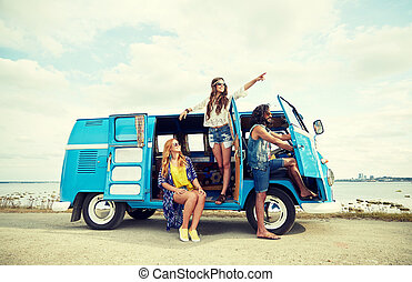 smiling young hippie friends over minivan car - summer...