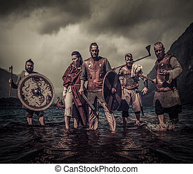 A group of armed Vikings standing on river shore - A group...