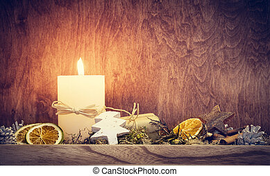 Chistmas decoration with candle glowing on wooden wall...