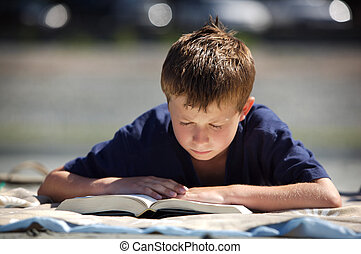 boy reading - young boy on a beach reading a book