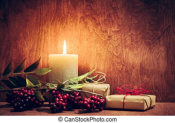 Chistmas presents, gifts with a candle glowing on wooden...