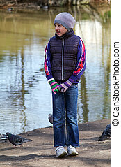 teenager girl standing betwin pigeons birds on the shore of...