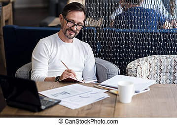 Smiling bearded man checking his agenda - Its done. Handsome...