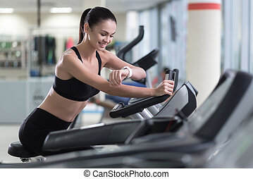 Active girl running on a treadmill and wearing smart watch