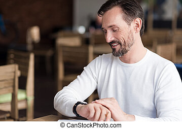 Smiling bearded man checking time in cafe - High time....