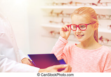 optician and girl choosing glasses at optics store - health...