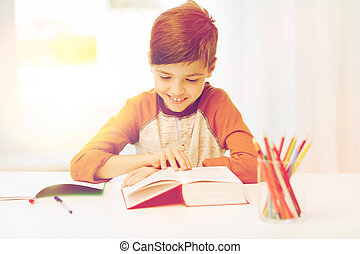 smiling, student boy reading book at home - education,...