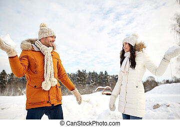 happy couple playing snowballs in winter - people, season,...