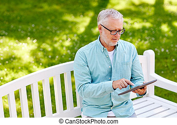 senior man with tablet pc at summer park - technology,...