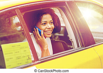 happy african woman calling on smartphone in taxi - business...