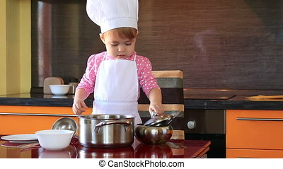small charming child in chef suit arranges the pasta on plates in the kitchen