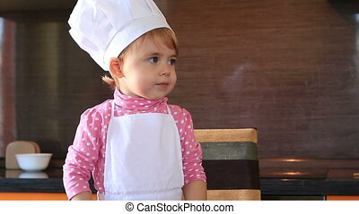 clouse-up portrait small child in chef suit helps her mother cook in the kitchen