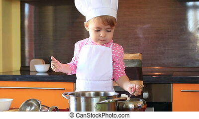 small charming child in chef suit sprinkles sugar food in...