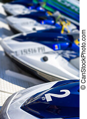 Jet Skis at a Coastal Resort - Row of blue and white jet...