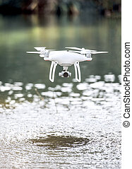 Drone quadcopter with camera flying above water. - Drone...