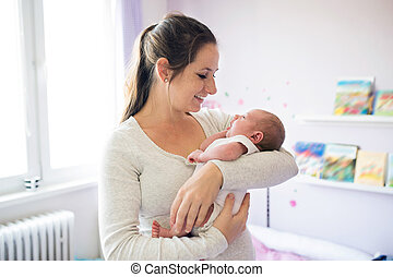 Beautiful young mother holding her son in her arms -...