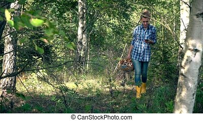 Worried mushroom picker woman using smart phone with gps to...