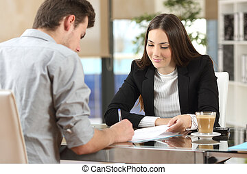 Client signing a document in an office with a businesswoman...