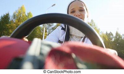 Young happy beautiful woman driving ATV through the sun,...