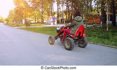 Young beautiful woman driving ATV, hand hold steering wheel...