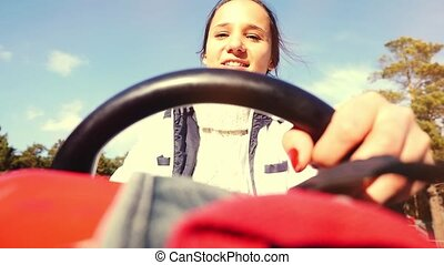 Young happy beautiful woman driving ATV, hands hold steering...