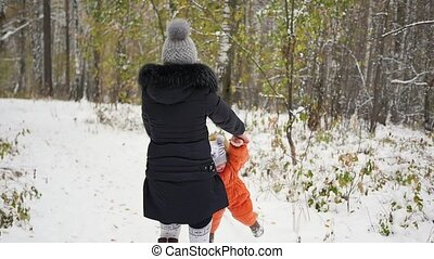 mother spinning child in winter Park