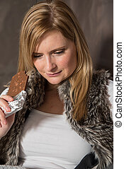 Woman sitting in a tent eating chocolate