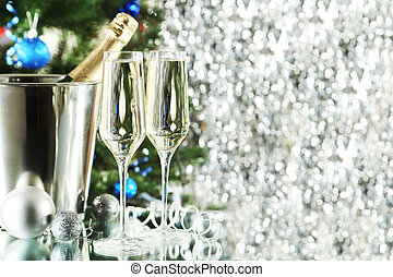 Glasses of champagne with bottle in a bucket on lights background