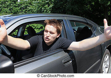 road rage - Angry young male driver yelling and gesturing to...